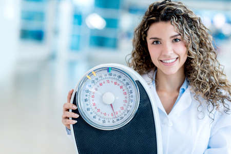 nutritionist: Female nutritionist at the hospital holding a weight scale