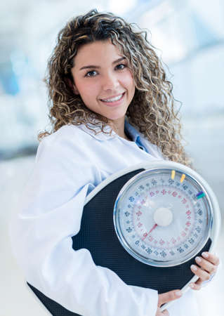 Female nutritionist with a weight scale at the hospital photo