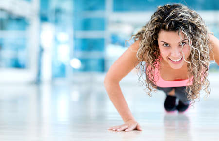 Woman exercising at the gym doing push ups photo