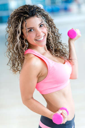 keeping: Happy woman lifting weights at the gym keeping fit