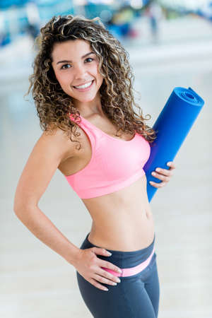 Fit woman at the gym holding yoga mat photo