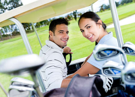 Happy couple in a cart playing golf photo