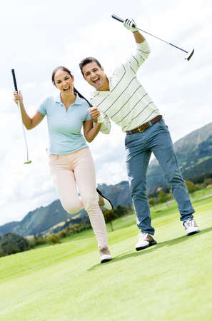 Couple playing golf looking very happy with arms up photo