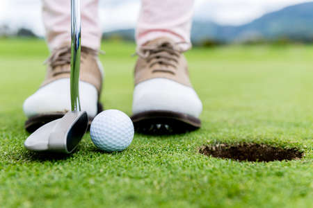 woman golf: Golf player at the putting green hitting ball into a hole