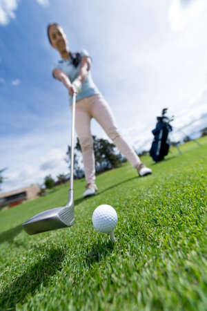 Woman playing golf at the course - focus on ball photo