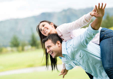 Beautiful couple outdoors with arms open like flying photo