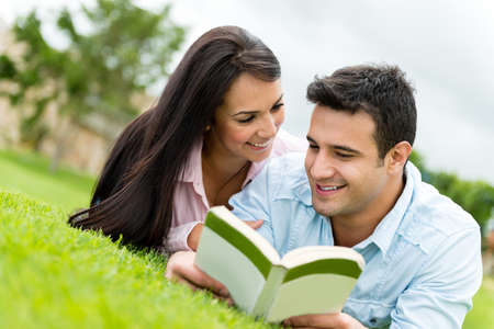 date book: Beautiful couple on a romantic date outdoors reading a book