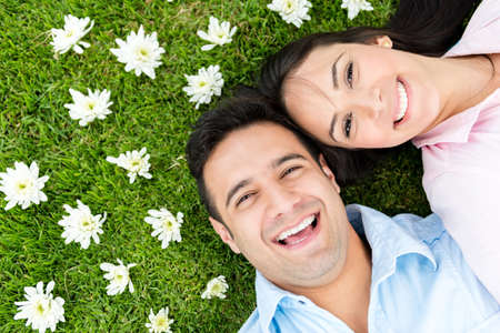 Beautiful portrait of a happy couple lying outdoors photo
