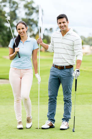 Happy couple playing golf at the course photo