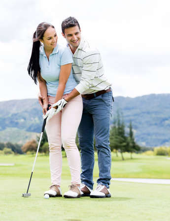 Man teaching woman how to play golf at the course photo