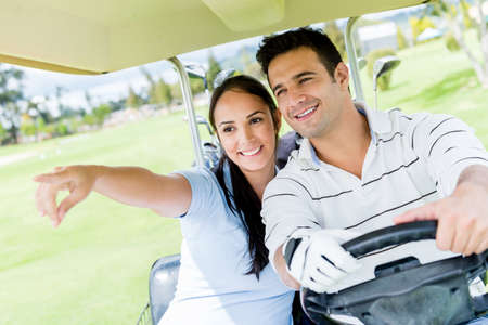Happy couple at the golf course driving a cart photo
