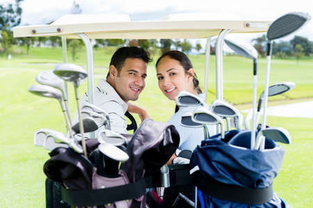 woman golf: Couple in a golf cart looking very happy