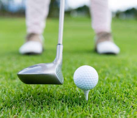 Golf player at the tee box hitting ball photo
