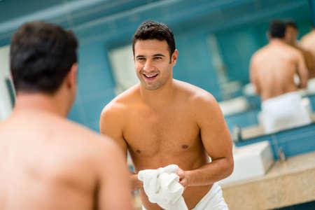 Schöner Mann in den Spiegel an der Badezimmer Lizenzfreie Bilder