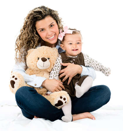 Cute mother and baby with a teddy bear looking happy - isolated over white photo