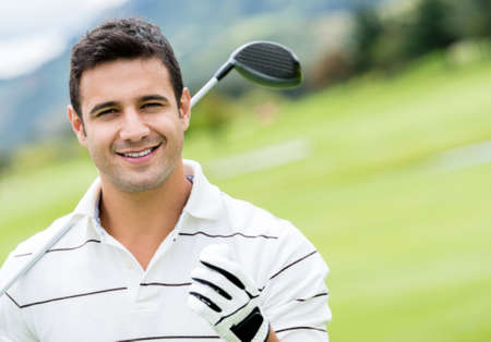 Handsome man playing golf and looking happy photo