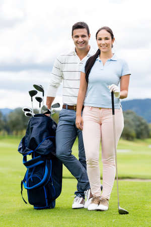 Couple playing golf looking very happy at the course photo