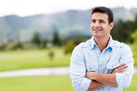 Nachdenklich Casual Mann im Freien suchen und lächelnd