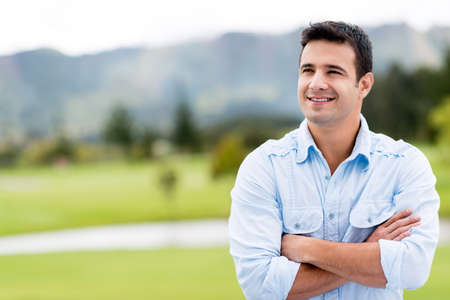 Thoughtful casual man outdoors looking up and smiling photo