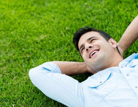Glücklicher Mann Entspannung im Freien auf dem Rasen lag Lizenzfreie Bilder