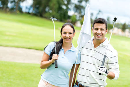 Couple at the course playing golf and looking happy photo