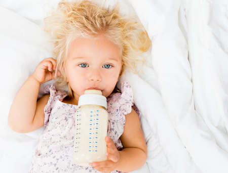 baby bottle: Portrait of a girl drinking from her baby bottle Stock Photo