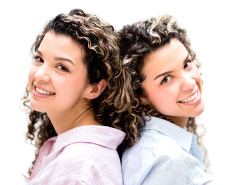 Beautiful twins smiling - isolated over a white background photo