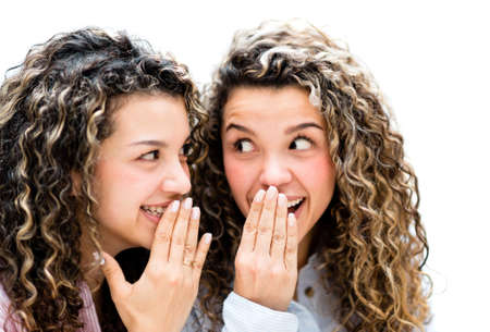 Happy twins sisters gossiping and looking suprised - isolated over white photo