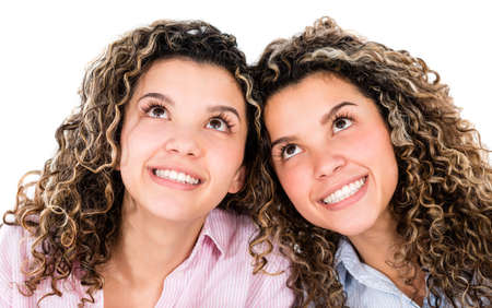 Thoughtful twins smiling and looking up - isolated over white background photo
