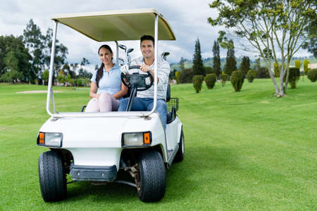 Couple in a golf cart at the course looking very happy photo