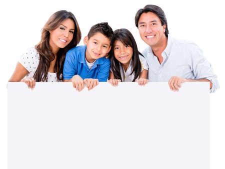 hispanic boy: Familia feliz sosteniendo un cartel y sonriendo - aislados en blanco Foto de archivo