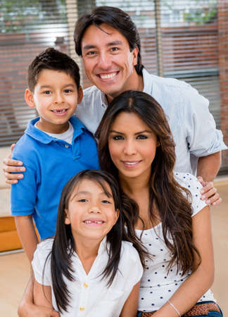 Portrait of a Latin family smiling at home looking very happy photo