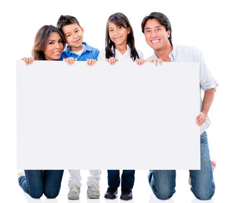 Glückliche Familie mit einem Plakat und lächelnd - isoliert über weiß Lizenzfreie Bilder