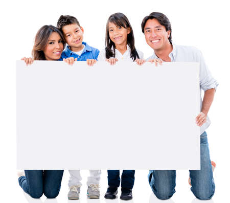 a placard: Happy family holding a placard and smiling - isolated over white