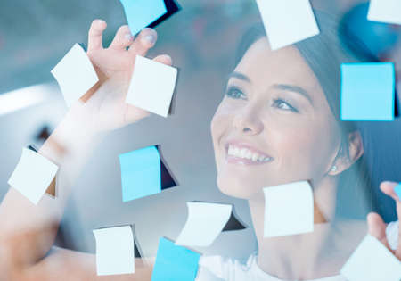 hectic: Happy woman multitasking with post-its all over the place