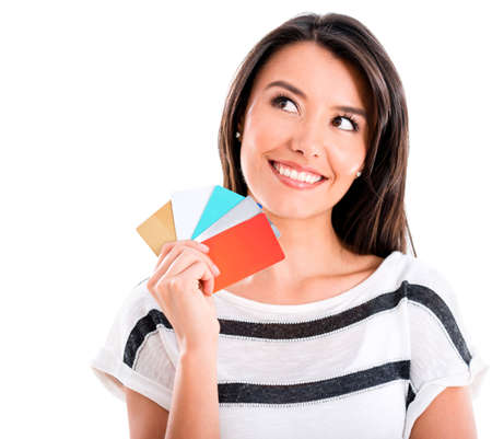 loyal: Thoughful shopping woman with credit cards - isolated over white