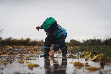 Cute little child playing in the puddle during rain. Happiness and pure bliss, not a single care in the world. Happy lifestyle moment in nature playing in the water with rubber boots on feet and love.