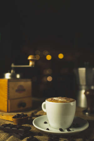 A cup of coffee, cappuccino. A nice composition with a coffee grinder, an espresso maker and some chocolate. Restaurant and coffee shop. Nice creamy bokeh.