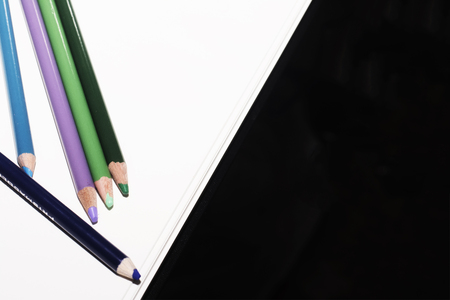 An arrangement of cool colored pencils on a paper white background Stock Photo