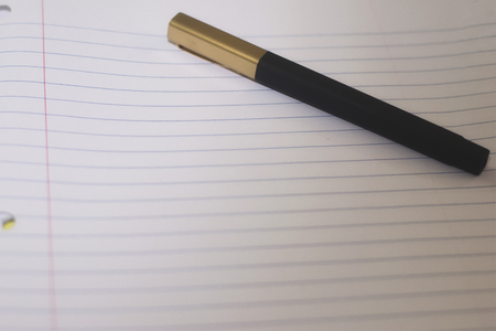 A single black pen on a lined peace of white paper, ready to go back to school or be an office supply.