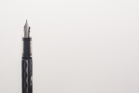 A fountain ink pen vertical on a white page background, with plenty of copy space. Stock Photo