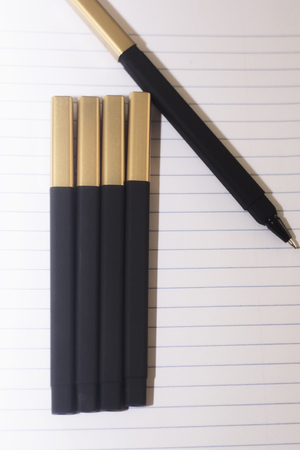 Black pens on a lined peace of white paper, ready to go back to school or be an office supply.