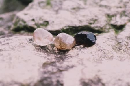 A group of smokey quartz on a rock.