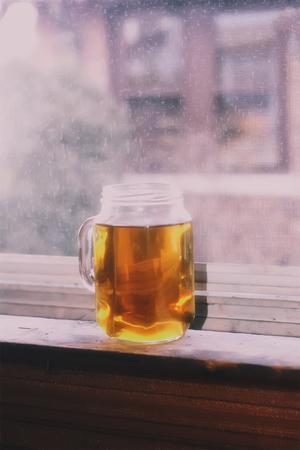 A jar of homemade tea on the windowsill.