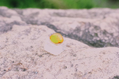 A side view of amber on a rock.