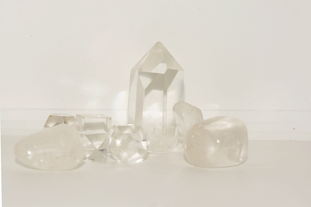 a group of clear quartz and smokey quartz together on a white background.