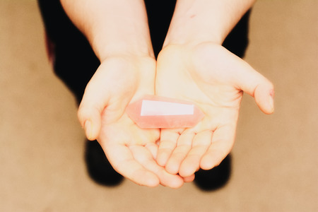A rose quartz being held in palms of hands. Stock Photo