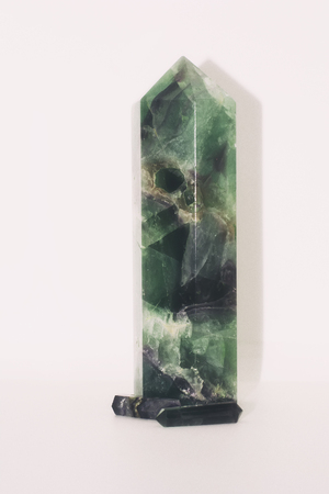 A close up of a big pillar of fluorite on a white background.