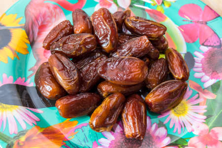 intestinal cancer: pile of dates on a floral plate Stock Photo