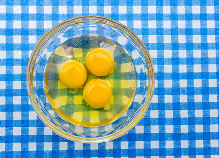 cracked raw organic eggs in a glass bowl